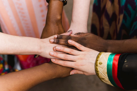 National diversity. People of different appearance and nationality stand in a circle together and hold hands. Team building and partnership business concept