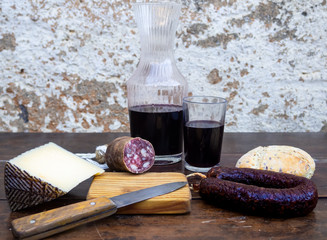 Iberian pork sausages on an old wooden board with a wedge of sheep cheese, an antique knife and a bottle and a glass of red spanish wine