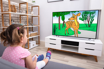 Little Girl Sitting On Sofa Watching Cartoon