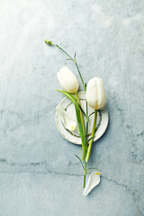 An arrangement of white tulips and dianthus flower bud on gray stone background. Floral decoratin. Flat lay. Copy space
