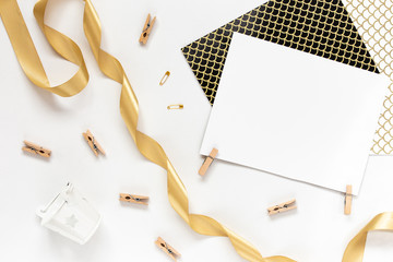 Top view on Beautiful greeting card idea with area for your text with golden ribbon, wooden clothespins copyspace, topview, mockup, flatlay