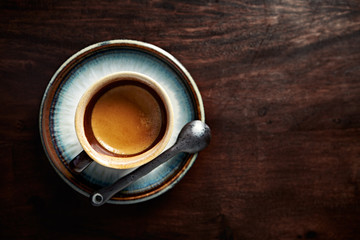 A cup of coffee on dark wooden background. Flat lay. Copy space