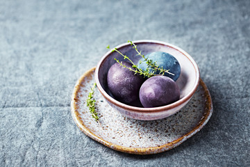 An arrangement of natural colored Easter eggs in ceramic bowl. Linen background. Copy space