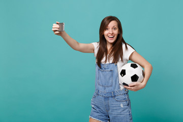 Excited young woman football fan with soccer ball doing selfie shot on mobile phone isolated on blue turquoise background. People emotions, sport family leisure lifestyle concept. Mock up copy space.