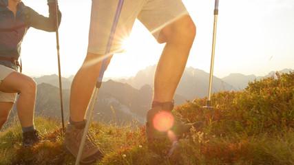 SUN FLARE CLOSE UP: Unrecognizable tourist couple exploring the scenic mountains