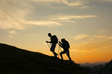 SILHOUETTE: Cheerful tourist couple are trekking up a grassy hill at sunset.
