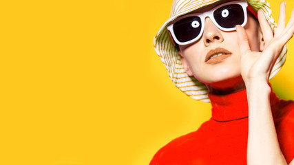 Beautiful young woman with sunglasses and hat, retro style on yellow. Summer holiday