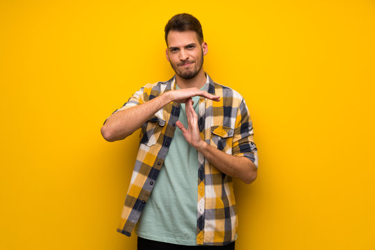 Handsome man over yellow wall making time out gesture