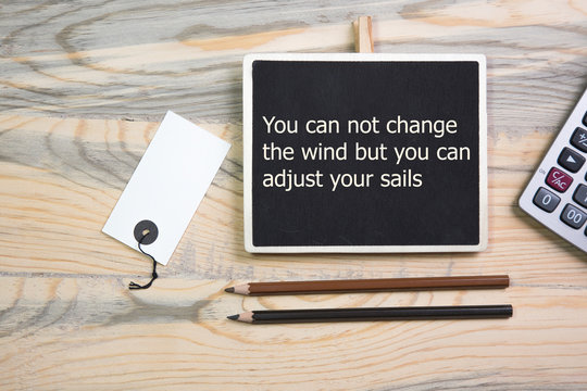 The text Motivational quote You can not change the wind but you can adjust your sails