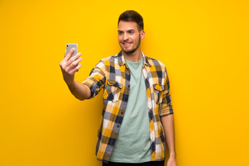 Handsome man over yellow wall making a selfie