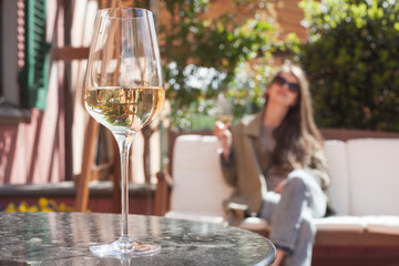 glass of chilled white wine on table over young woman and Tuscany backgound