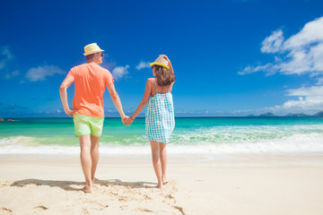 Couple in bright clothes on a tropical beach at Mahe, Seychelles.