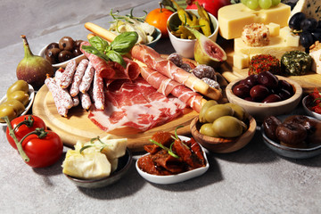 Italian antipasti wine snacks set. Cheese variety, Mediterranean olives, crudo, Prosciutto di Parma, salami and wine in glasses over grunge background.