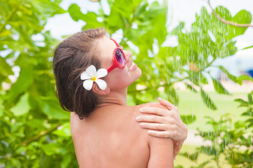 young woman with frangipany flower in hair refreshing in tropical shower
