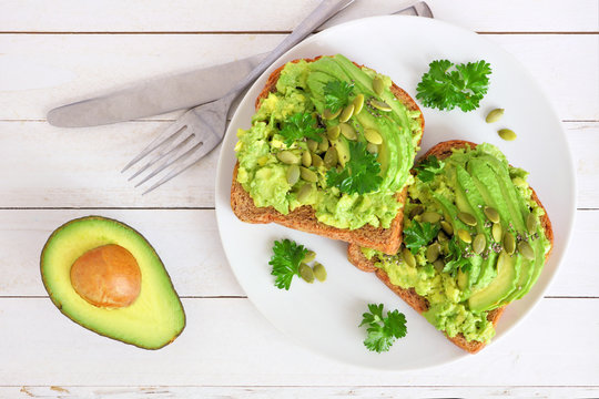 Avocado toasts with pumpkin and chia seeds on whole grain bread. Above view on a white wood background.