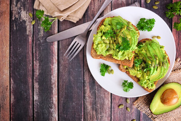 Avocado toasts with pumpkin and chia seeds on whole grain bread. Top view, corner border against a dark wood background.