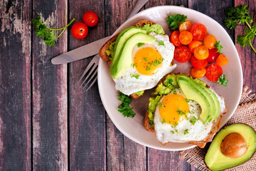 Avocado toasts with eggs and tomatoes on whole grain bread. Top view, corner border against a dark wood background.