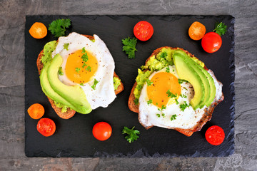 Avocado toasts with eggs and tomatoes on whole grain bread. Top view on a dark slate background.