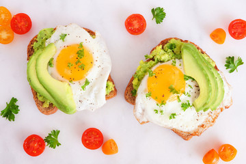 Avocado toasts with eggs and tomatoes on whole grain bread. Top view on a bright marble background.