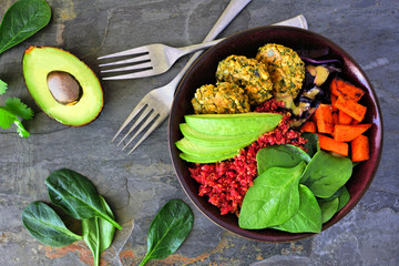 Healthy vegan lunch bowl with falafels, beet quinoa, avocado, and vegetables on a dark stone background. Healthy eating concept. Overhead scene.