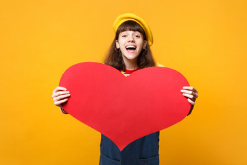 Laughing girl teenager in french beret, denim sundress holding big empty blank red heart isolated on yellow wall background in studio. People sincere emotions, lifestyle concept. Mock up copy space.