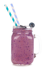 Blueberry smoothie in a mason jar glass with paper straws isolated on a white background