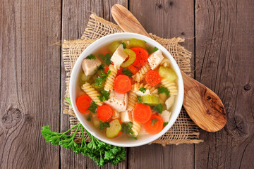 Homemade chicken noodle soup with vegetables. Top view on a old rustic wood background.