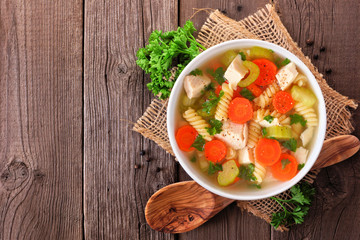 Homemade chicken noodle soup with vegetables. Top view on an rustic old wood background.