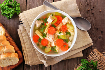 Homemade chicken noodle soup with vegetables. Overhead table scene on a wood background.