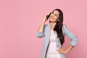 Pretty young woman in striped jacket talking on mobile phone, conducting pleasant conversation isolated on pink pastel wall background. People sincere emotions lifestyle concept. Mock up copy space.