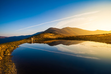 Mountain lake landscape at sunset with peak reflection scenic view