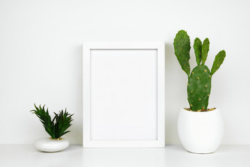 Mock up white frame with cactus and succulent plants on a shelf or desk. White shelf and wall. Portrait frame orientation.