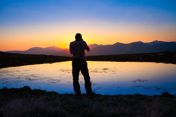 Photographer on the side of the lake beautiful landscape at sunset
