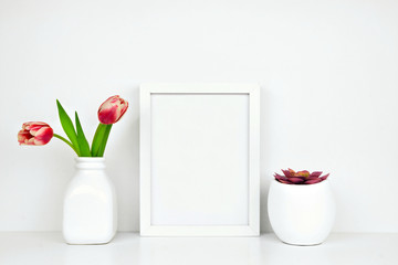 Mock up white frame with succulent plant and tulip flowers on a shelf or desk. White shelf and wall. Portrait frame orientation.
