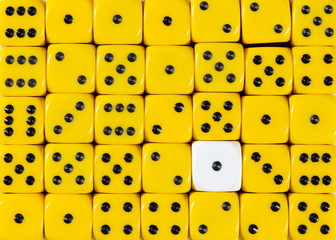 Background of random ordered yellow dices with one white cube