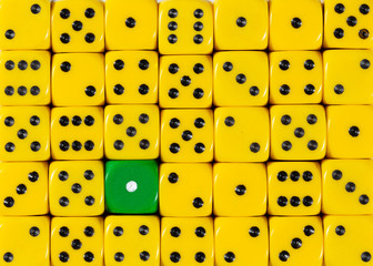 Background of random ordered yellow dices with one green cube