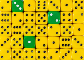 Background of random ordered yellow dices with three green cubes