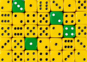 Background of random ordered yellow dices with four green cubes