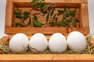white eggs on straw in a wooden box.