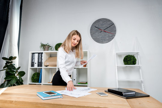 Theme business woman at work. Beautiful young caucasian woman business man working standing in the office near the table, checks edits financial charts on paper