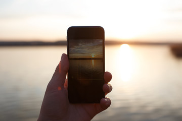 Male hand holding smartphone and taking the photo of sunset.