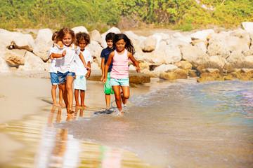 Happy children running on the beach in summer
