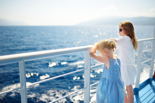 Adorable young girls enjoying ferry ride staring at the deep blue sea. Children having fun on summer family vacation in Greece.