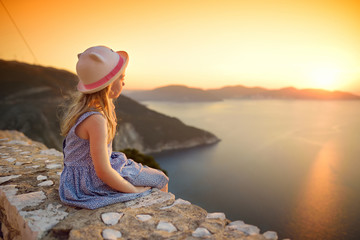 Cute little girl enjoying the view of picturesque jagged coastline of Kefalonia on summer sunset.