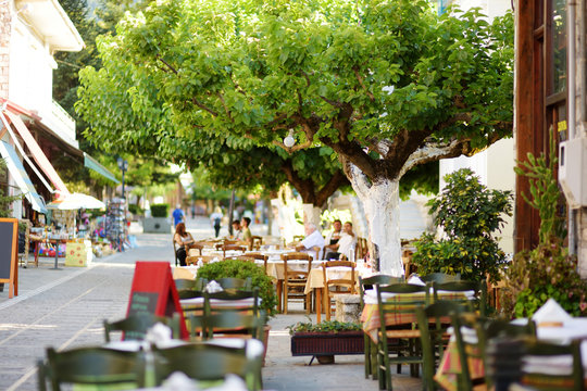 Small outdoor restaurants at the pedestrian area at center of Kalavryta town near the square and odontotos train station, Greece.