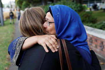 A woman embraces the relative of a victim after Friday's mosque attacks, outside Masjid Al Noor in Christchurch