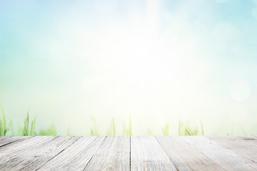 Wall Mural - Background with green grass and sunny blue sky over wooden deck