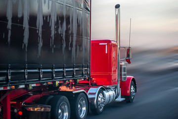 Bright red big rig semi truck with covered semi trailer going on the road for delivery Wall mural