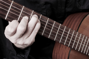 Guitarist plays the guitar. Close-up.