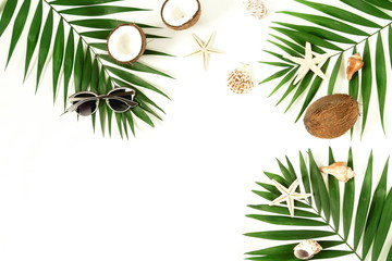 top view travel background. tropical green palm branches pattern frame, coconut, seashells, stars, sunglasses on a white background. copy space.abstract.